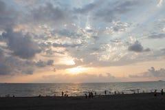 Coucher du soleil d'or de bel été ci-dessus Avec les vagues calmes et la réflexion du soleil sur la plage Un peuple sur la plage  Images libres de droits
