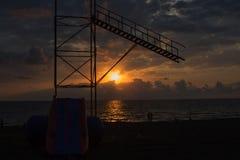 Coucher du soleil d'or de bel été ci-dessus Avec les vagues calmes et la réflexion du soleil sur la plage Un peuple sur la plage  Photos stock