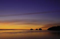 Coucher du soleil d'or derrière trois roches de voûte Images stock