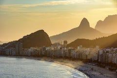 Coucher du soleil d'or entre les bâtiments de Copacabana Image libre de droits