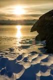Coucher du soleil d'hiver près des roches avec la neige le lac congelé Baikal Photographie stock