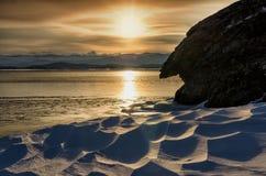 Coucher du soleil d'hiver près des roches avec la neige le lac congelé Baikal Photos libres de droits