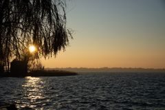 Coucher du soleil d'hiver sur le lac Ciel avec la lumière égalisante chaude image stock