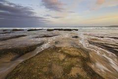 Coucher du soleil d'océan avec de l'eau se précipitant Photo libre de droits