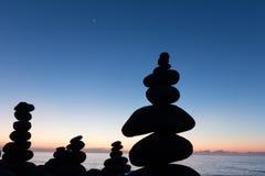 Coucher du soleil d'océan avec la silhouette en pierre empilée Images stock