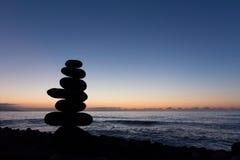 Coucher du soleil d'océan avec la silhouette en pierre empilée Photo stock