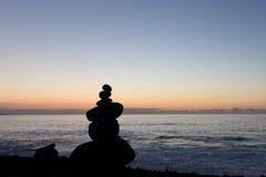 Coucher du soleil d'océan avec la silhouette en pierre empilée Photo libre de droits