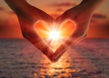 Coucher du soleil dans des mains de coeur Photographie stock libre de droits