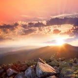 Coucher du soleil dans l'horizontal de montagnes Ciel dramatique, pierre colorée Photos libres de droits