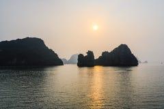 Coucher du soleil dans la baie long d'ha, Vietnam Formations de roche, humeur brumeuse, coucher du soleil et refections en mer de photo libre de droits