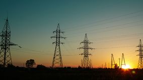 Coucher du soleil dans la campagne à côté de la route et des voitures de dépassement parmi les lignes électriques à haute tension clips vidéos