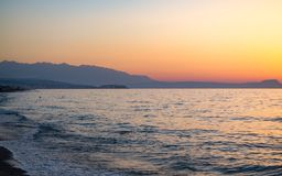 Coucher du soleil dans la plage de la mer Égée dans la station de vacances d'Adelianos Kampos, île de Crète, Grèce Images stock