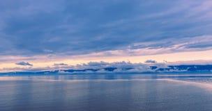 Coucher du soleil dans le calme sur le lac et le bateau lentement de flottement Image libre de droits
