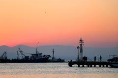 Coucher du soleil dans le port Pêche de silhouettes, bateaux avec la cargaison et fond de phare image stock