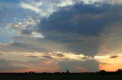 Coucher du soleil dans le village Orange de ciel nuageux photographie stock libre de droits