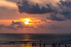 Coucher du soleil de Bali avec des personnes sur la plage photographie stock libre de droits