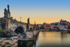 Coucher du soleil de château et de Charles Bridge de Prague Photographie stock