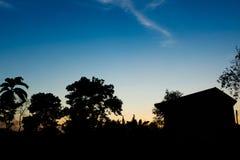 Coucher du soleil de ciel bleu avec le siluate de l'arbre et de la maison photographie stock