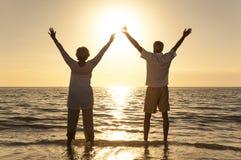 Coucher du soleil de couples d'homme supérieur et de femme sur la plage Photos libres de droits