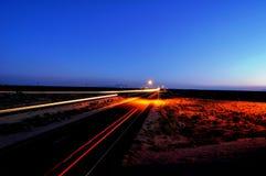 Coucher du soleil de désert avec des véhicules dans la tache floue de mouvement Photos stock