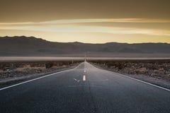 Coucher du soleil de désert le long de la route ouverte Images stock