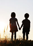 Coucher du soleil de deux enfants romantique Image libre de droits