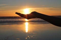 Coucher du soleil de fixation de main Photographie stock