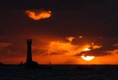 Coucher du soleil de Guernesey derrière le phare de Hanois Images libres de droits