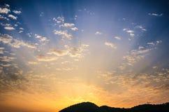 Coucher du soleil de jour d'été le beau avec le ciel coloré nuageux d'or et le soleil rayonnant étonnant rayonne venir par derriè Images libres de droits