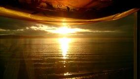 Coucher du soleil de l'eau, par une fenêtre curtained photographie stock libre de droits