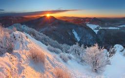Coucher du soleil de l'hiver en montagne avec des nuages Images stock