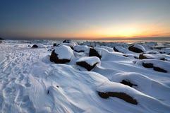 Coucher du soleil de l'hiver en plage pierreuse de Vidzeme Photos stock