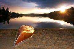 Coucher du soleil de lac avec le canoë sur la plage Photo stock