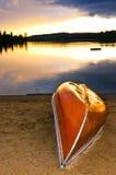Coucher du soleil de lac avec le canoë sur la plage images libres de droits