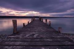 Coucher du soleil de lac avec le pilier en bois Photo stock