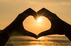 Coucher du soleil de lever de soleil de coeur de main Images libres de droits