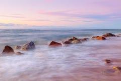 Coucher du soleil de mer et grands rochers collant de la mer onduleuse lisse photographie stock