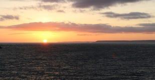 Coucher du soleil de mer et nuages de champ et oranges bruns Photographie stock