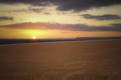 Coucher du soleil de mer et nuages de champ et oranges bruns Photo stock