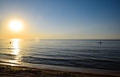 Coucher du soleil de mer Les gens se baignent le soir au coucher du soleil en mer Images libres de droits
