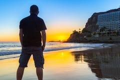 Coucher du soleil de observation d'homme au-dessus de l'Océan Atlantique Images stock