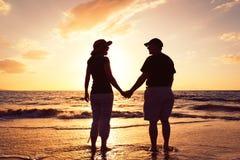 Coucher du soleil de observation de couples à la plage Photos libres de droits