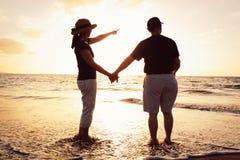 Coucher du soleil de observation de couples à la plage Photos stock