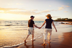 Coucher du soleil de observation de couples à la plage Image stock