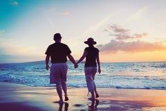 Coucher du soleil de observation de couples à la plage Images stock