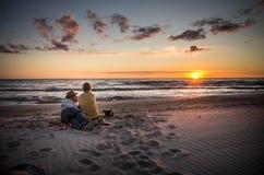 Coucher du soleil de observation de couples affectueux Photographie stock