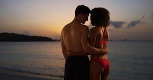 Coucher du soleil de observation de couples avec du charme de métis de plage Photographie stock libre de droits