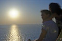 Coucher du soleil de observation de couples romantiques Photo libre de droits