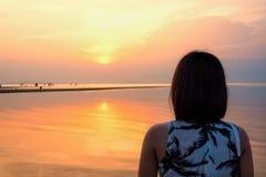 Coucher du soleil de observation de femme à la plage Photos stock
