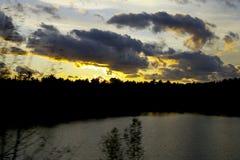 Coucher du soleil de pays de maison au-dessus de lac Photo stock